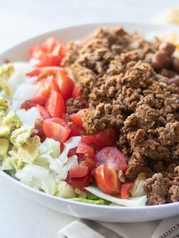 Taco Salad in white bowl with avocado, onion, tomatoes and ground beef