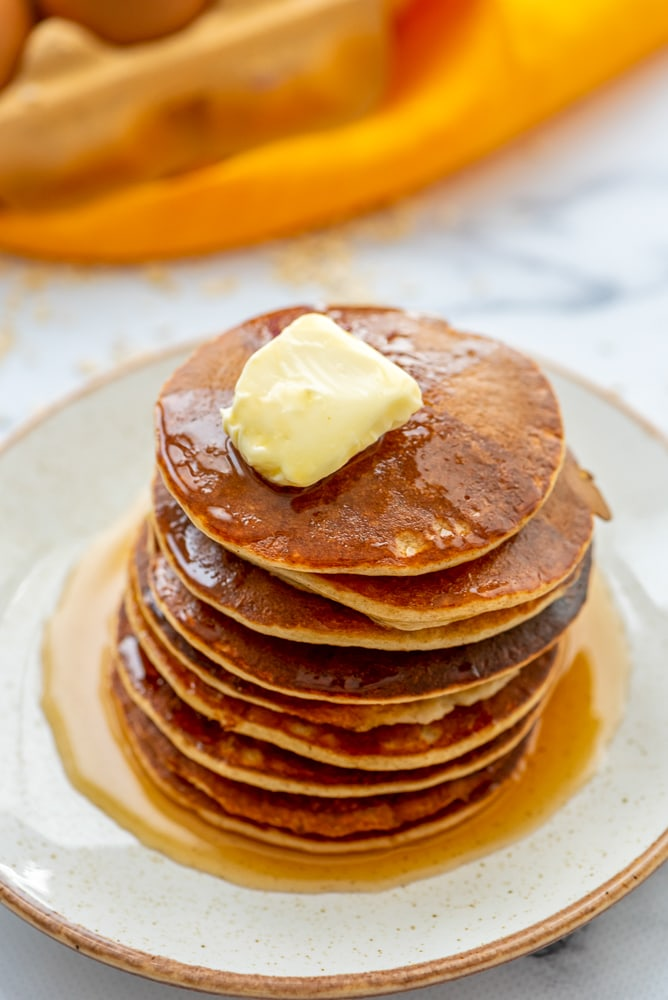 Banana Oatmeal Pancakes stacked on white plate with butter ans syrup