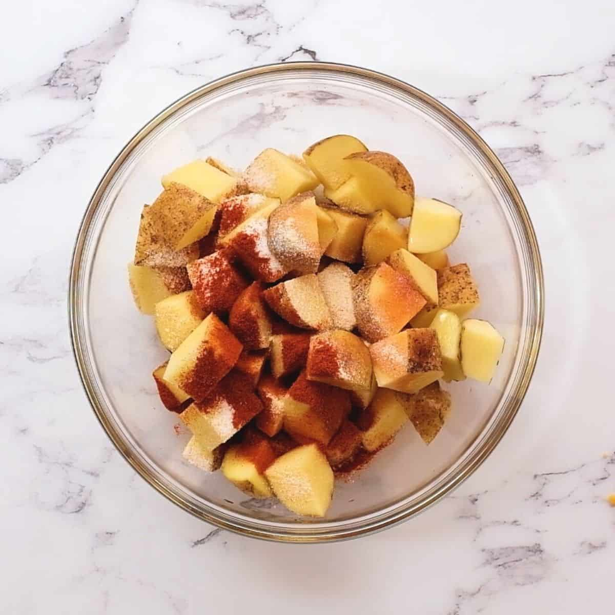 potatoes with buffalo seasonings in a clear bowl.