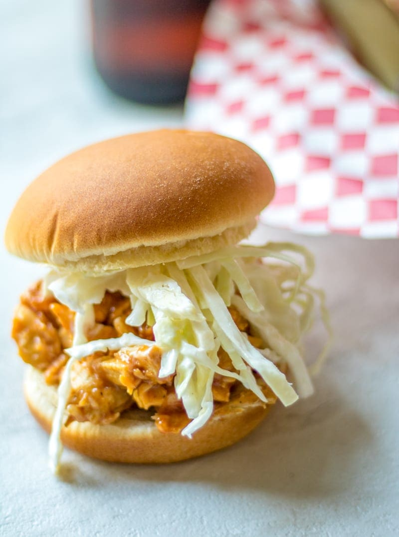 pulled pork on hamburger bun with slaw peeking out sides of bun.