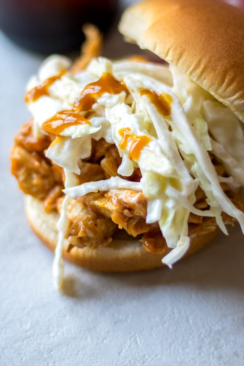 close up of pulled pork sandwich topped with slaw and drizzle of bbq sauce