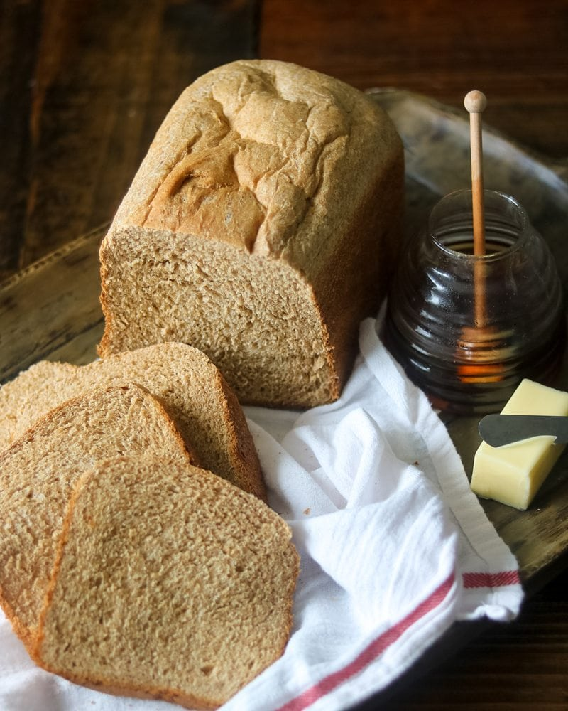 Egg Free Whole Wheat Bread Recipe baked and sliced on wooden platter with butter and honey to the side.