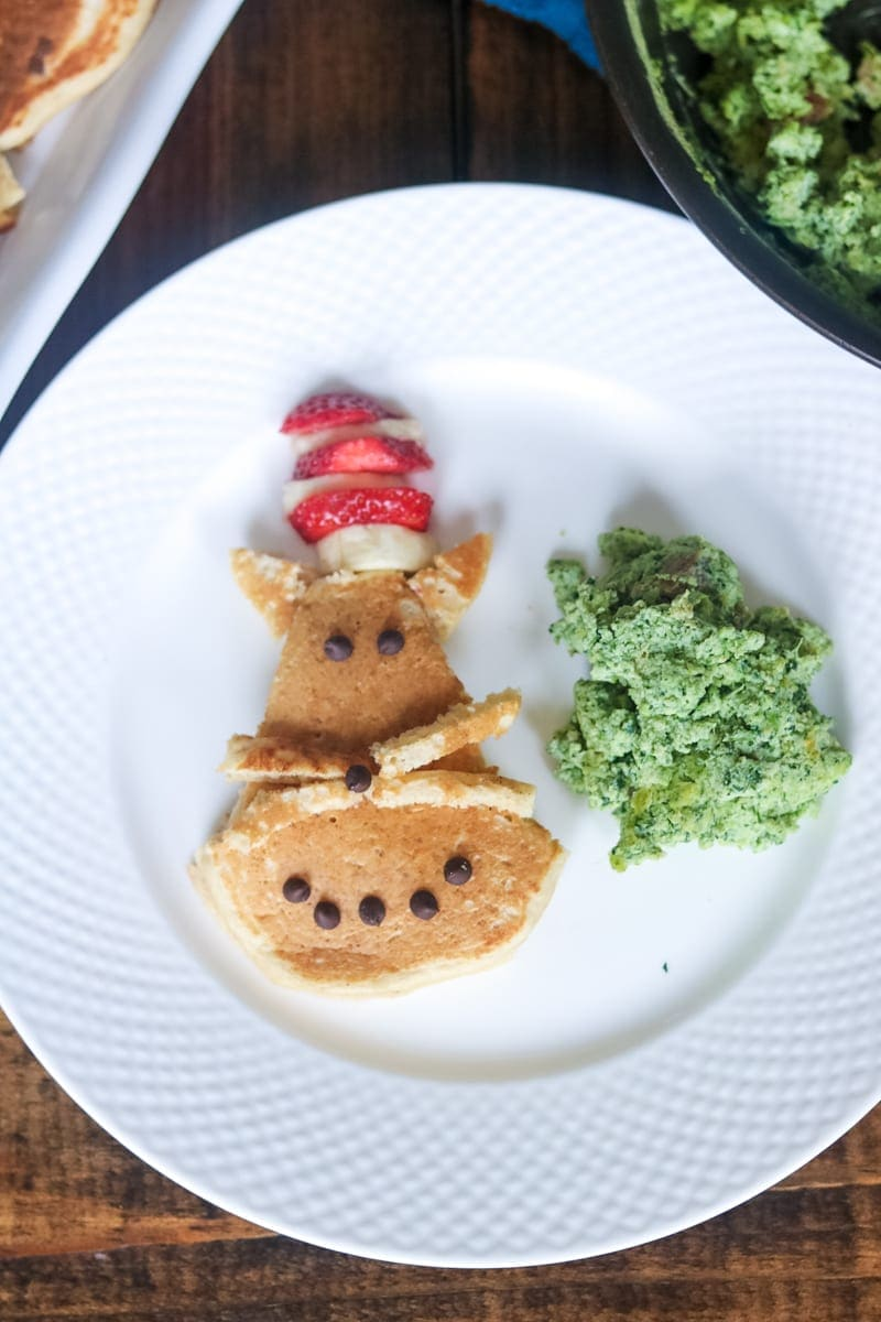 pancakes made to look like cat in the hat pancakes with green eggs and ham on white plate