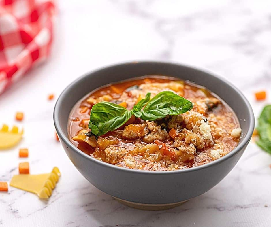 Bowl of lasagna soup topped with basil.
