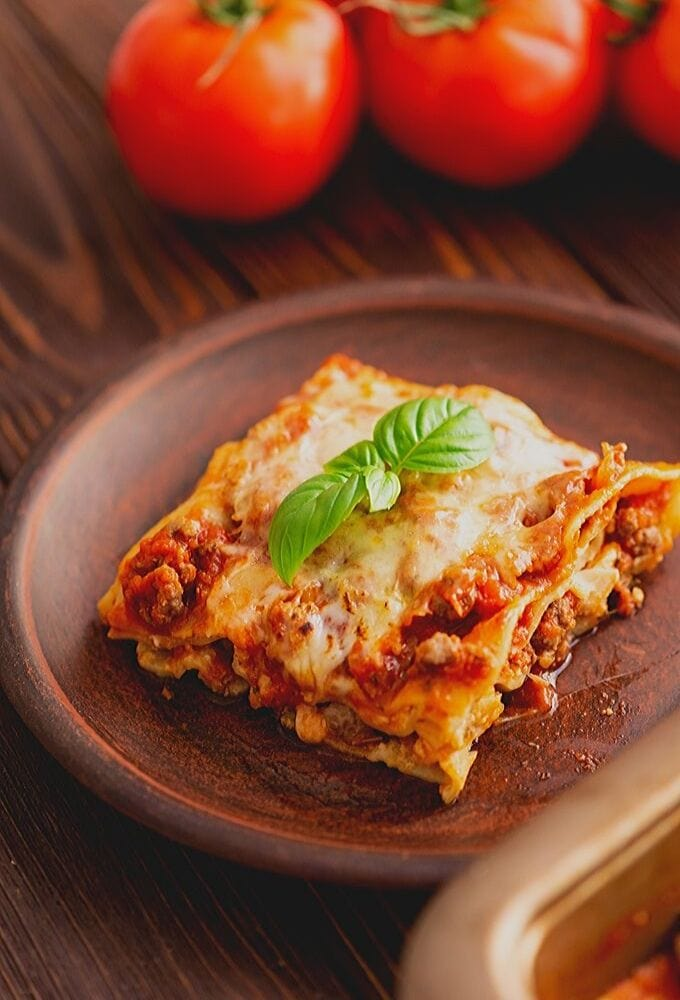 Slice of Homemade Lasagna on plate topped with basil