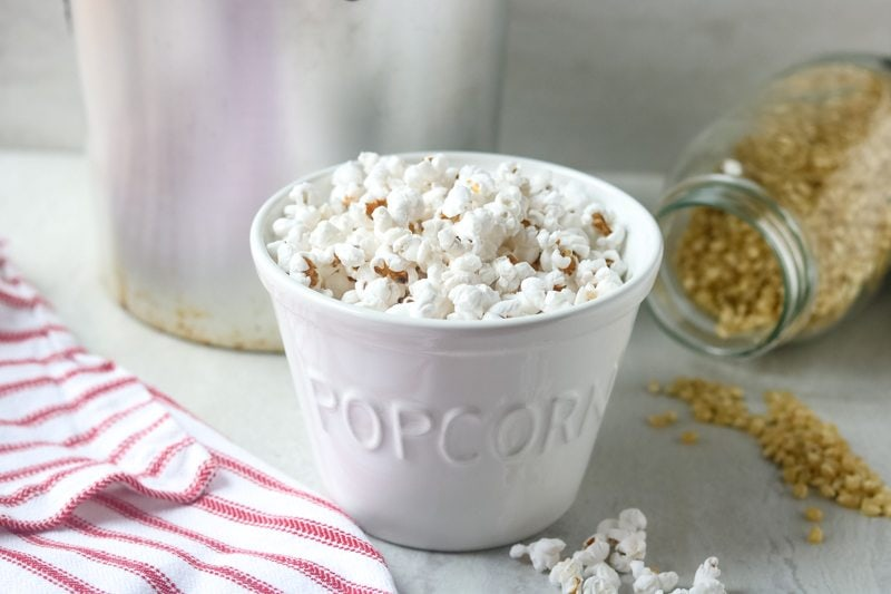 Stovetop popcorn in a white bowl that says popcorn with kernels and stovetop popper in background