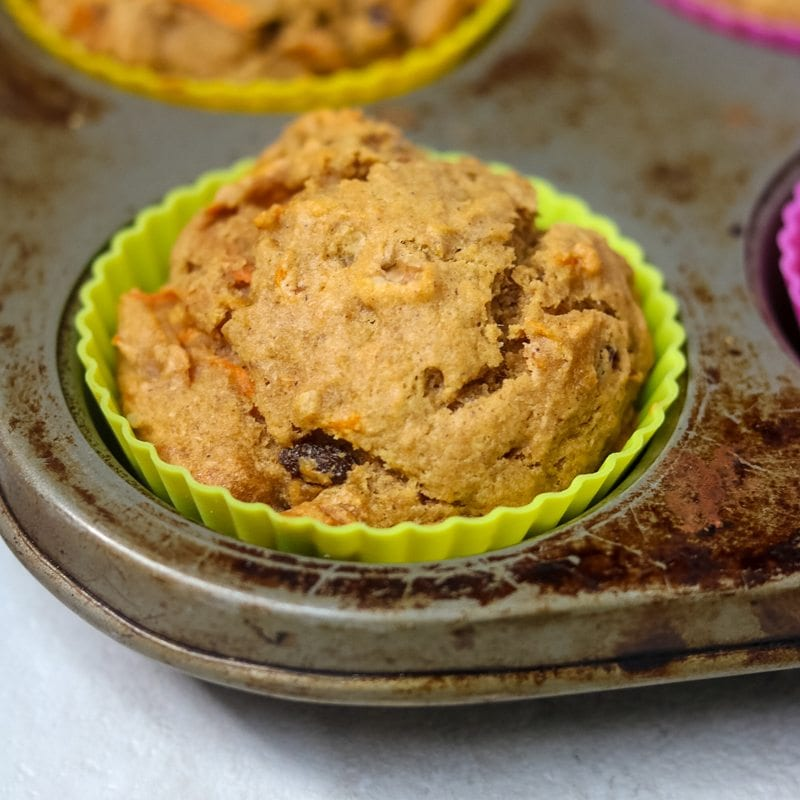 Close up on one baked carrot cake muffin in silver baking tin