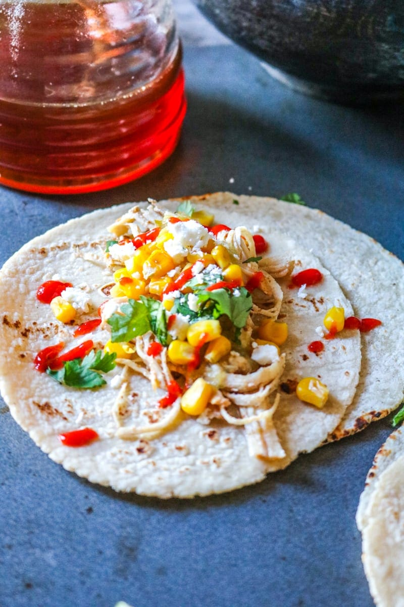 Crock pot chicken fajitas topped with corn and salsa verde