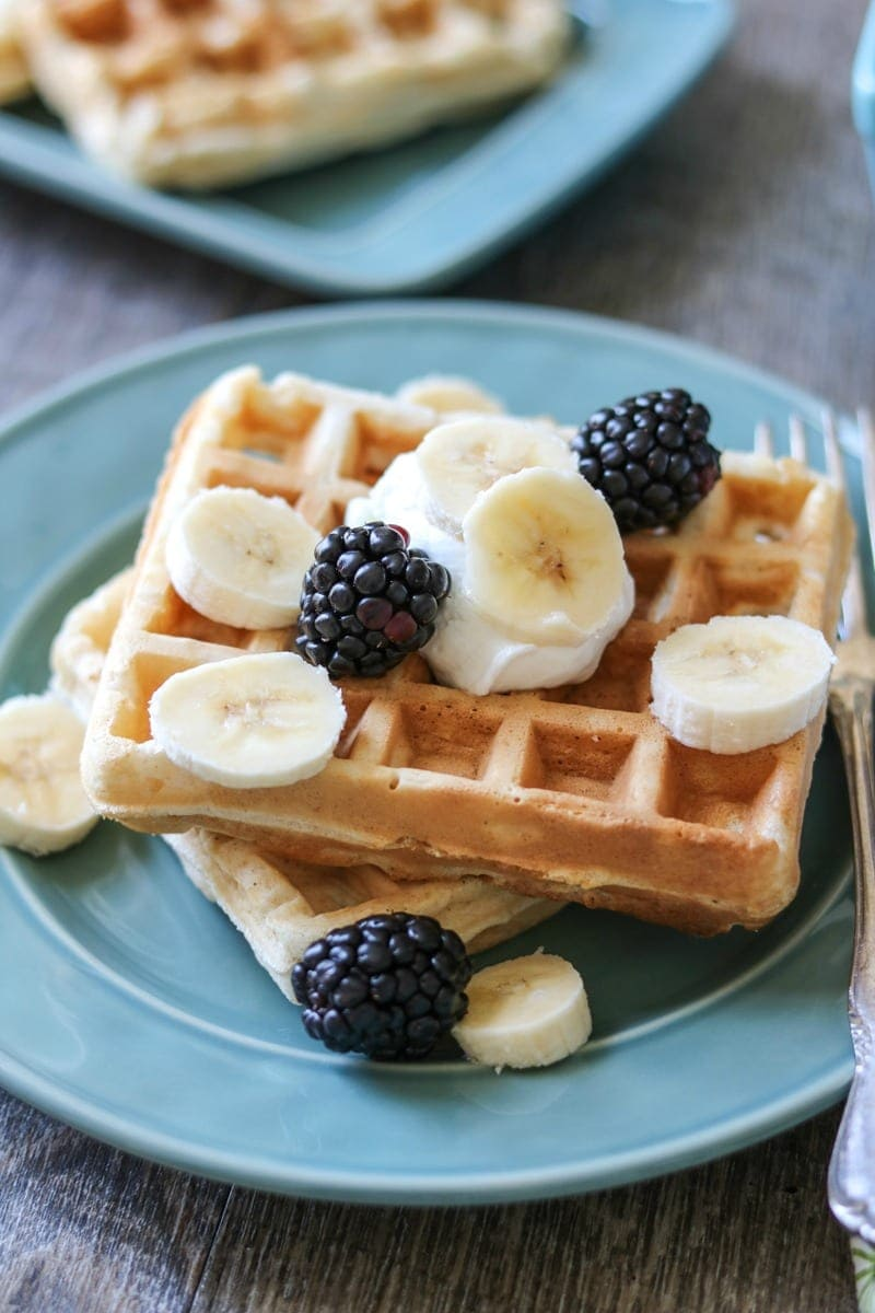 Blue plate with waffles topped with fresh fruit
