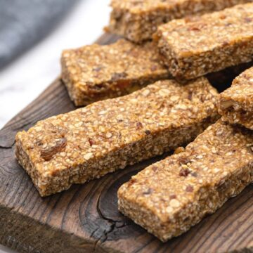4 Chewy Gluten Free Granola Bars on parchment paper with oats and dates to the side