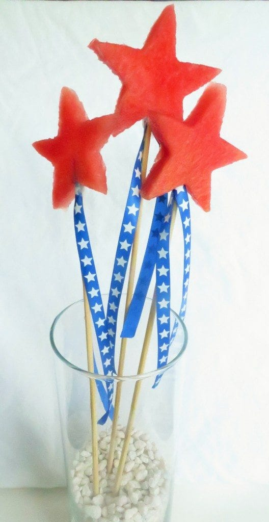 Making watermelon festive using cookie cutters, ribbon, and skewers.