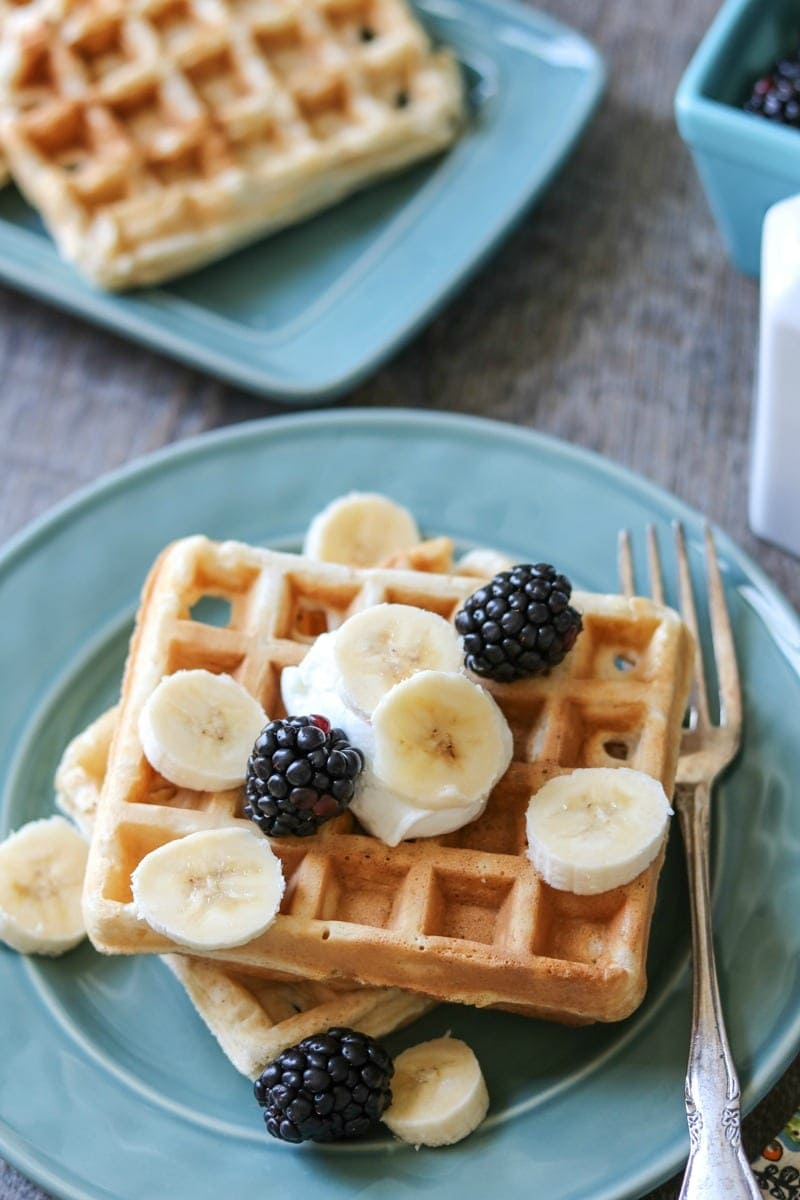 Golden homemade waffles on blue plate with fresh fruit