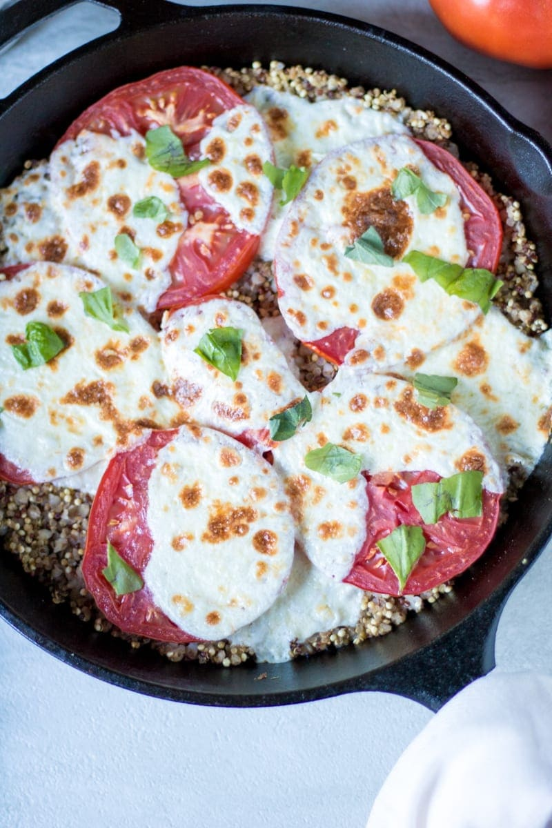Mozzarella Tomato Quinoa Bake in cast iron skillet topped with fresh basil