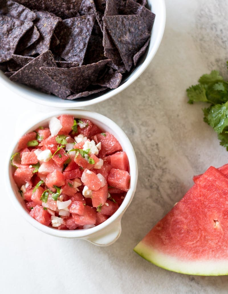 Watermelon and Feta Salsa in white bowl next to blue corn chips