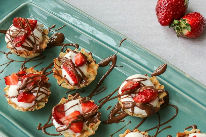 Tray of phyllo cups filled with strawberries, yogurt and chocolate