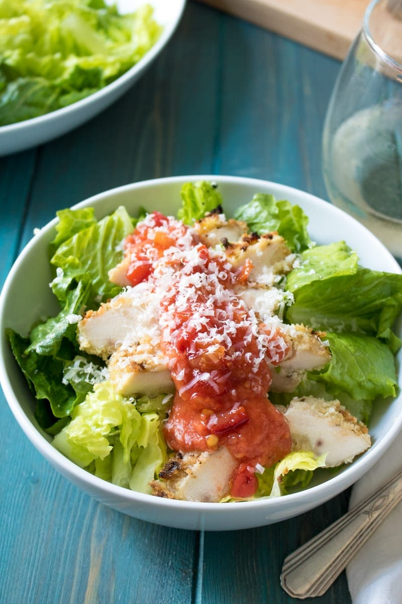 Chicken Parmesan Salad: A favorite classic has been given a fresh update in this Chicken Parmesan Salad. Crispy baked chicken sits atop a base of a salad tossed with a creamy dressing, finished with fresh tomato sauce. This dish knocks it out of the park!