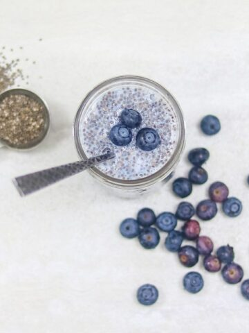 A jar of chia seed pudding on a white table with chia seeds and blueberries scattered around it.