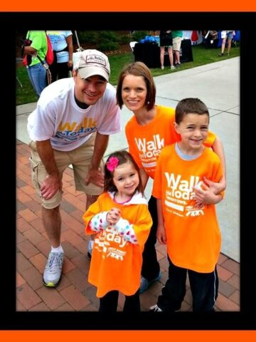 Kristen and her family at a cystic fibrosis walk with black and orange frame around photo