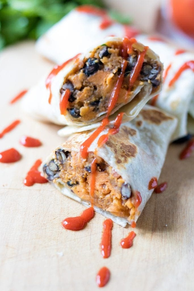 Black Bean and Sweet Potato Burritos with Bonus Stuffed Tomato: Cook once and eat twice! A spicy filling of black beans and sweet potatoes are stuffed into burritos and then morphed into a completely new meal by being stuffed into tomatoes.