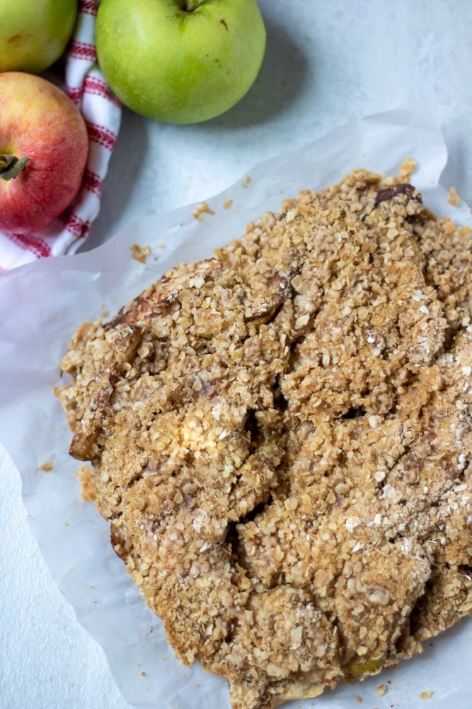Baked Apple Pie Bars with Oat Crumble next to fresh apples