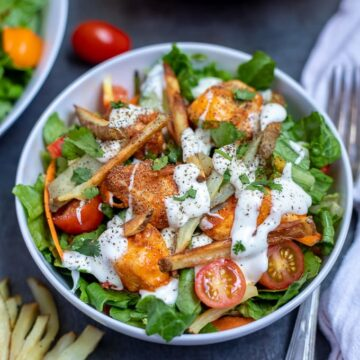 Bowl with salad topped with buffalo chicken, ranch and fries