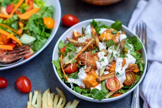 Buffalo Chicken Salad with Oven Baked Fries: Baked chicken strips that have been seasoned with buffalo seasoning are tossed into a salad topped with oven baked fries.