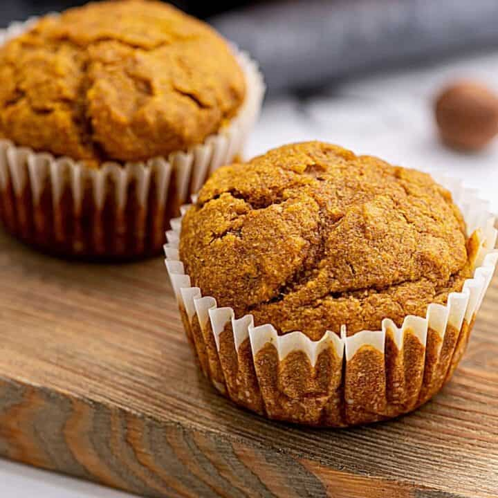 Baked Whole Wheat Pumpkin Muffins on wooden cutting board