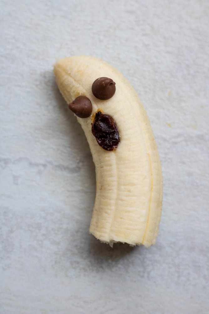 Banana with chocolate chip eyes and raisin mouth