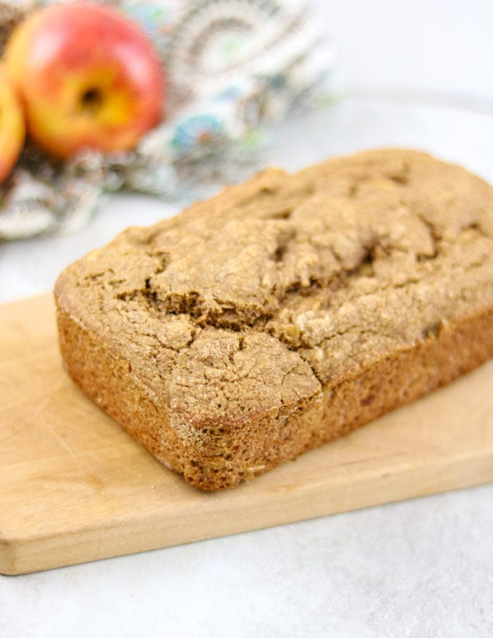 Loaf of whole wheat apple bread on wooden cutting board.