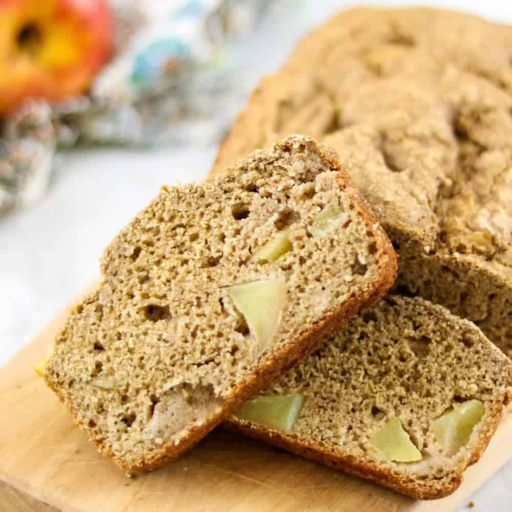 Slice of whole wheat apple bread showing chunks of large apples