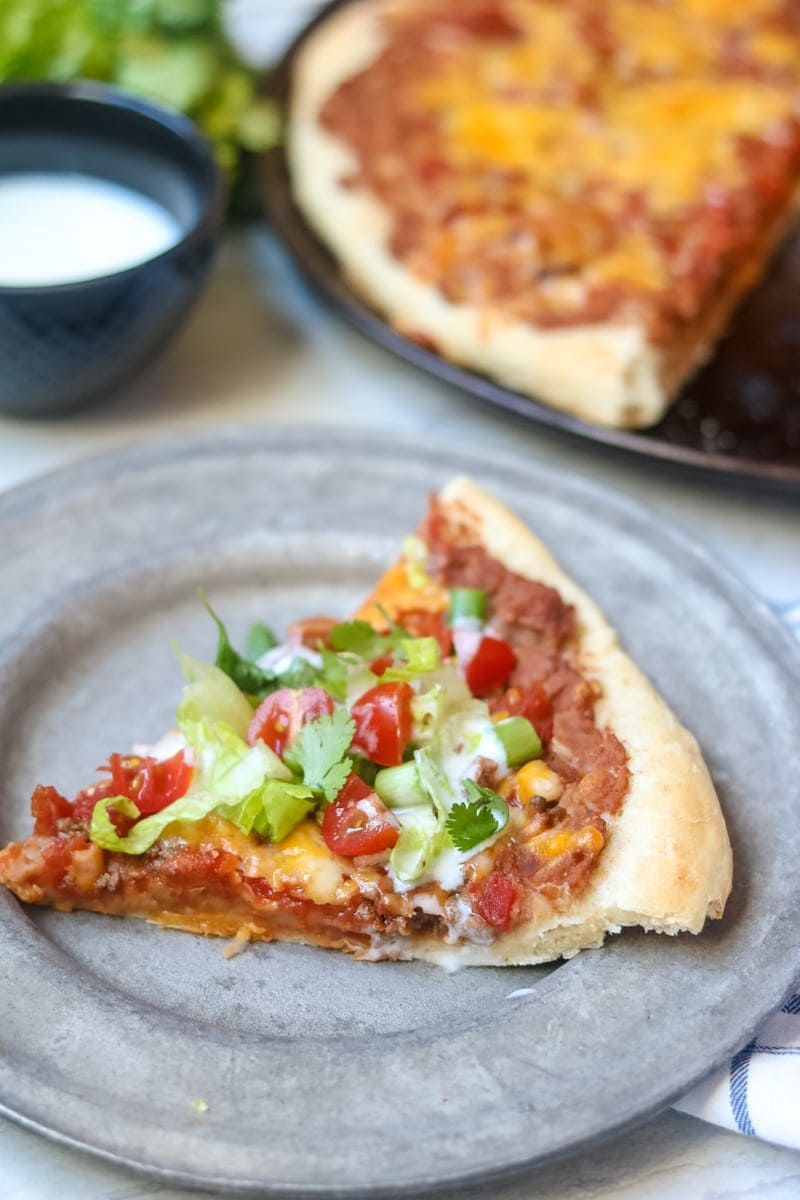 Slice of homemade taco pizza sitting on silver plate topped with fresh tomatoes, lettuce.