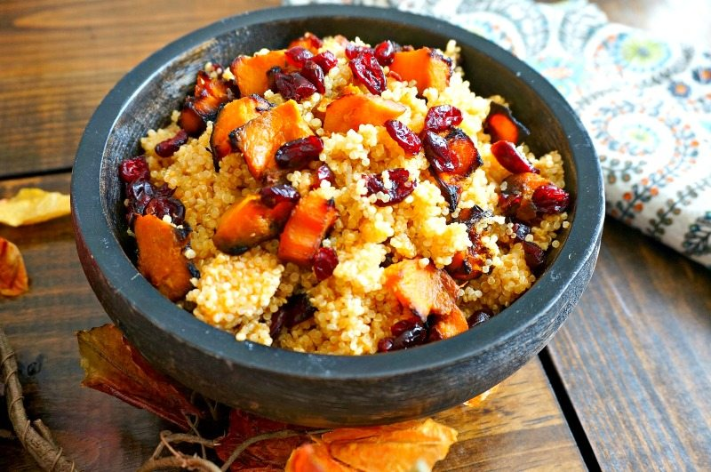 Black wooden bowl filled with butternut squash quinoa salad