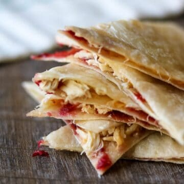 Sliced up turkey quesadilla with cranberry sauce