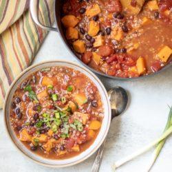 Black bean sweet potato chili in bowl next to dutch oven with sweet potato chili