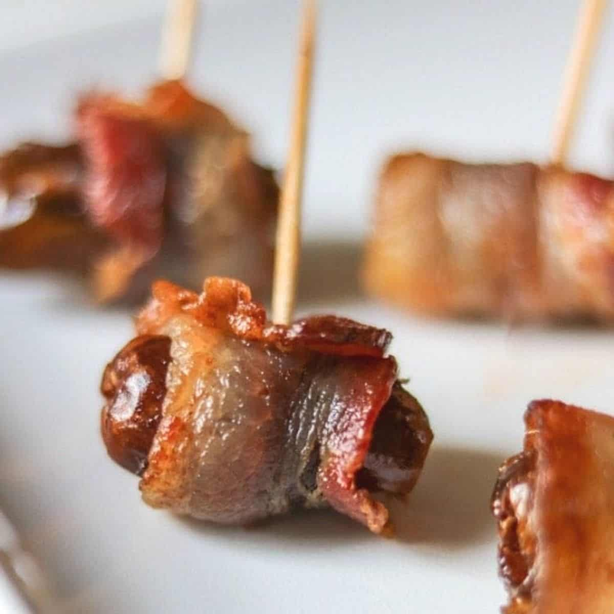 Close up of bacon wrapped date stuffed with almond on white baking tray.