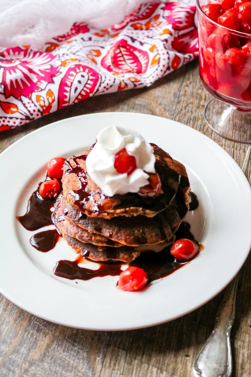 White Plate with 4 chocolate pancakes stacked on top of eachother with chocolate sauce and cherry sauce and whipped cream.