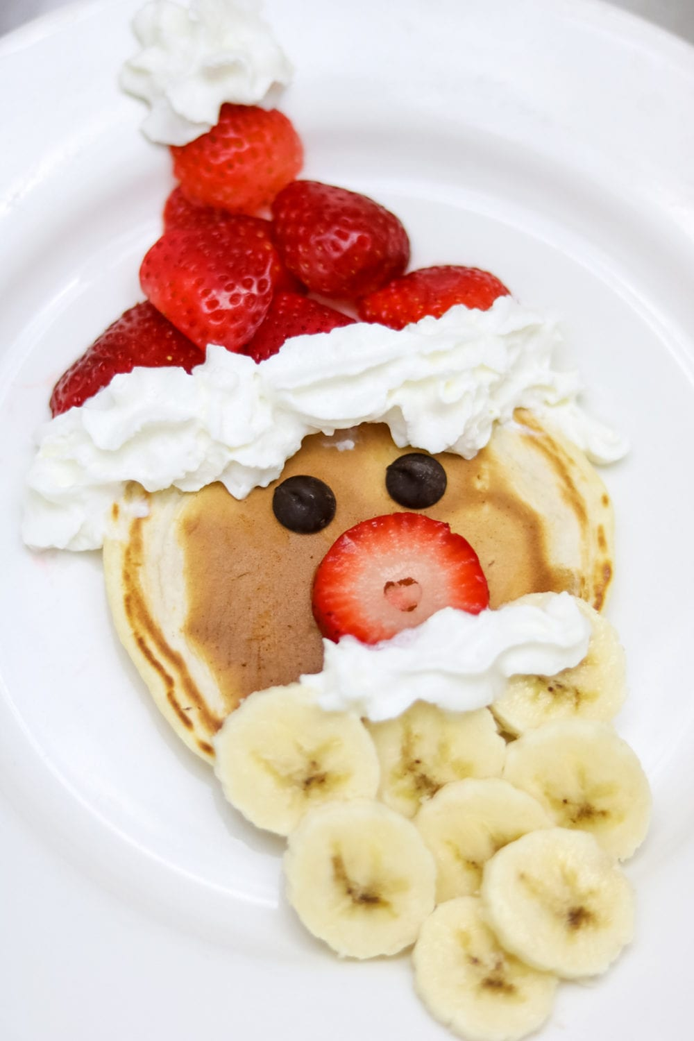Easy Fruit Santa Pancakes: Santa is made with banana beard and strawberry hat.