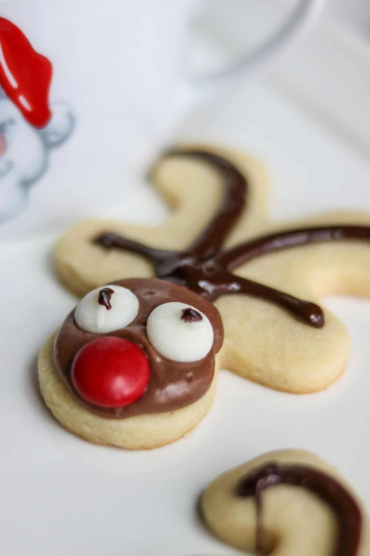 A gingerbread cut out cookie turned upside down and decorated like a reindeer..