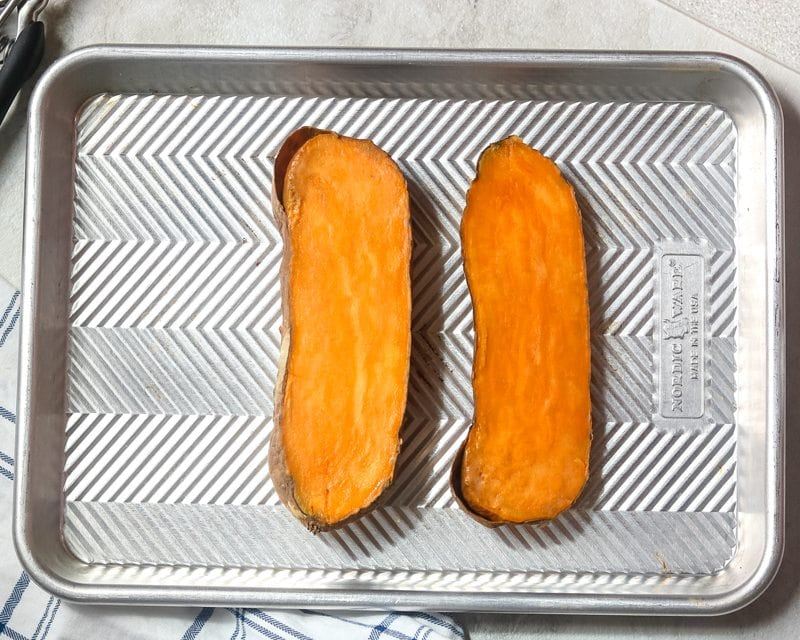 Baked sweet potato cut in half on cookie sheet