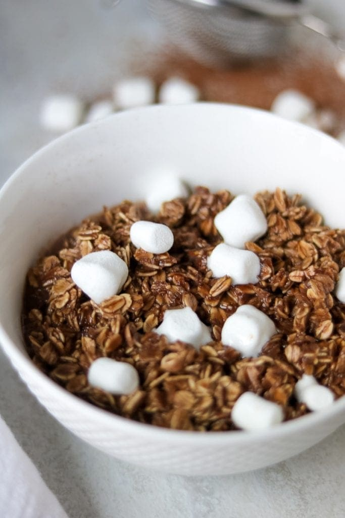 Chocolate Oatmeal in a white bowl topped with mini marshmallows