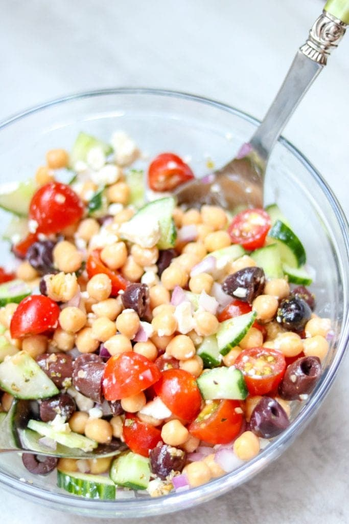 Mediterranean Chickpea Salad in glass bowl with serving spoons