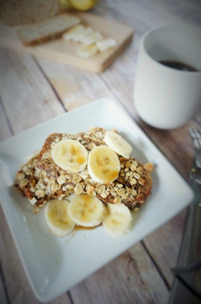Crusted Banana Bread French Toast on a white plate with fresh bananas