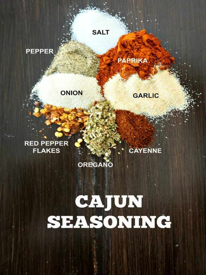 dried spices on wooden board each on labeled with text overlay that reads cajun seasoning