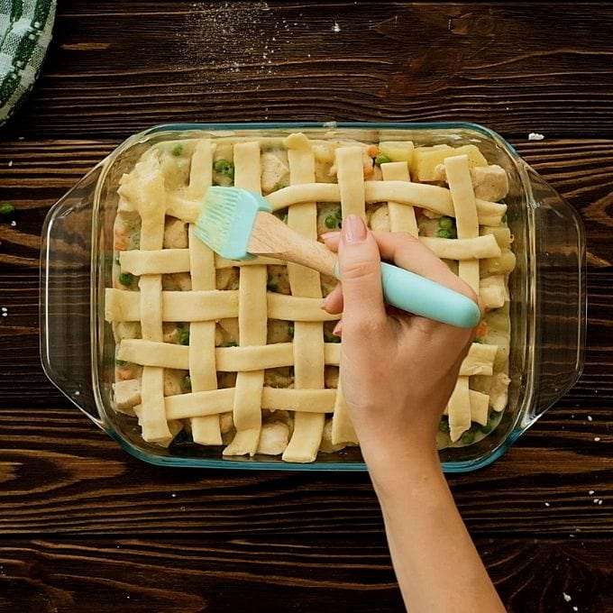Pastry brush brushing egg over lattice crust