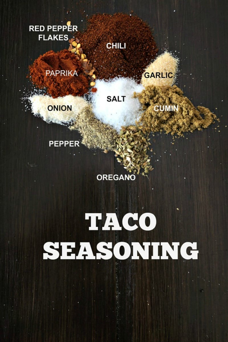 Taco Seasoning Text on wooden board with dried spices on board.