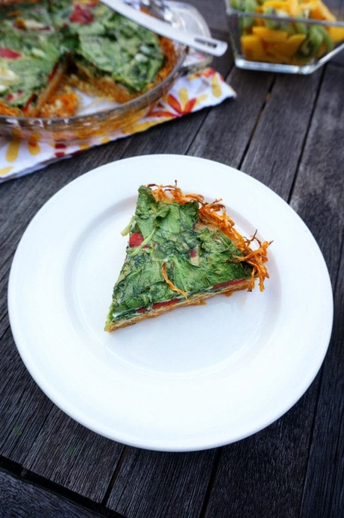 Top view of spinach quiche with sweet potato crust on wooden table next to fruit salad.