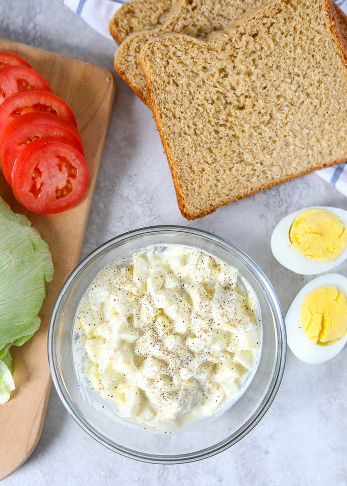 Bowl of Egg Salad next to bread and sliced tomatoes