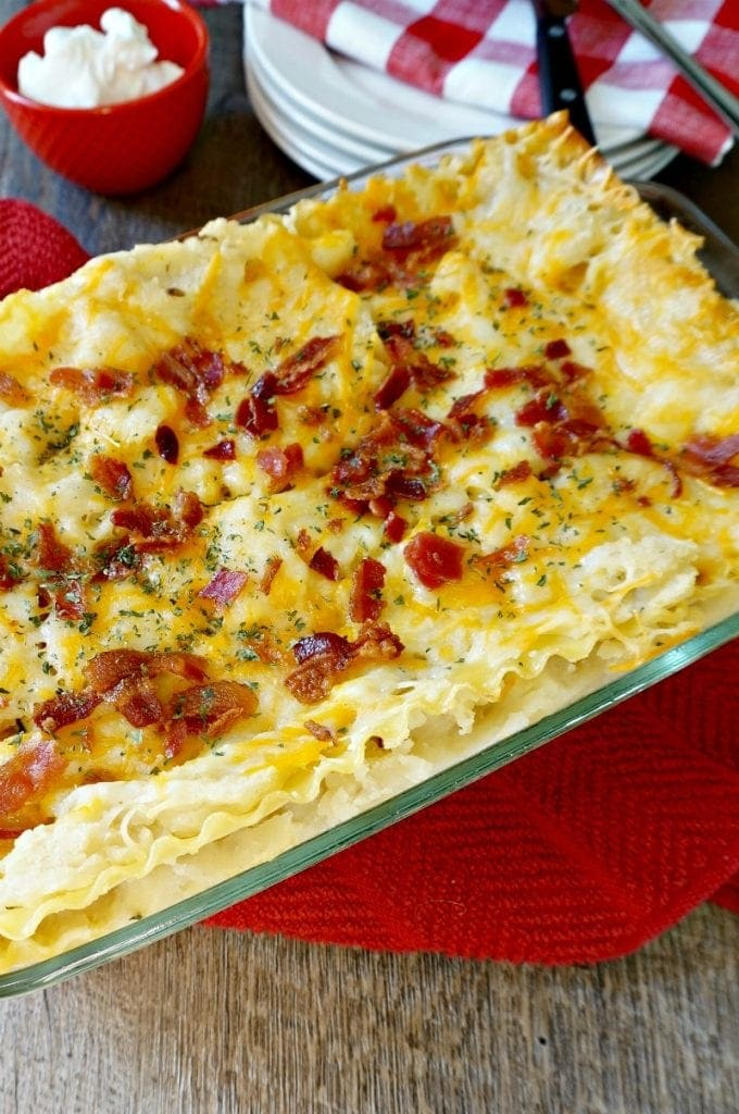 Baked Pierogi Lasasgna topped with crumbled bacon next to white plates and serving utensils