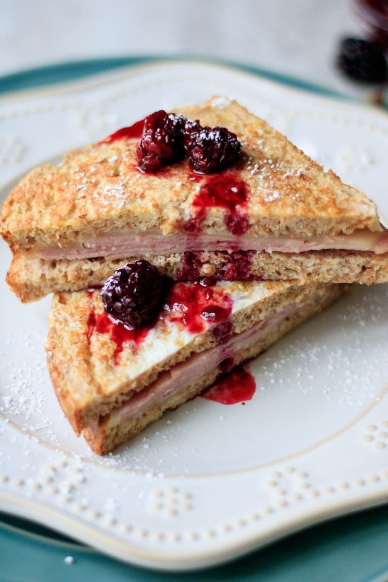 Monte Cristo sandwich cut open on white plate with blackberry sauce