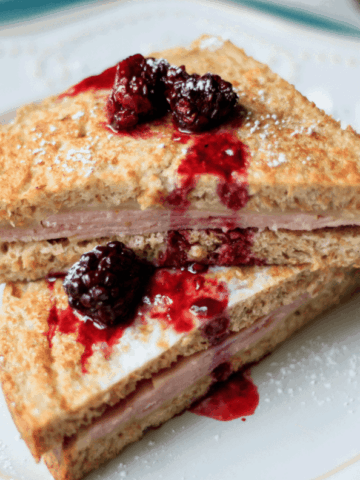 Monte Cristo with Fresh Blackberry Sauce on white plate